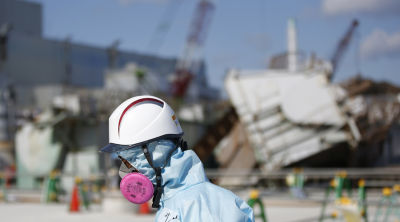 A Tokyo Electric Power Co. (TEPCO) employee, wearing a protective suit and a mask, walks in front of the No. 1 reactor building at TEPCO's tsunami-crippled Fukushima Daiichi nuclear power plant