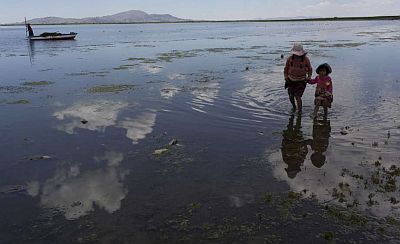 cousins from the Avila family search for discarded toys on the shores of Lake Titicaca, in Coata in the Puno region of Peru