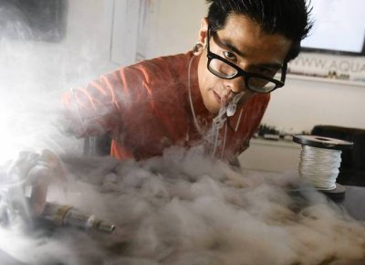 Aaron Flores exhales water vapor from an electronic cigarette