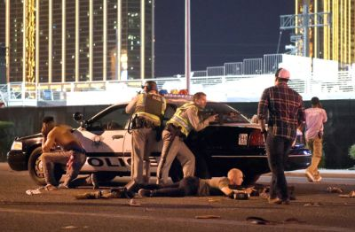 Orange County Sheriff deputies Brandon Mundy (left) and Garrett Eggert (on the ground) assist Las Vegas police officers