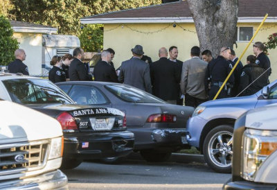 Police investigate the discovery of the remains of a female found Thursday afternoon in a refrigerator in a garage at a Santa Ana residence